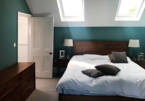 A domestic bedroom with painted walls and ceiling